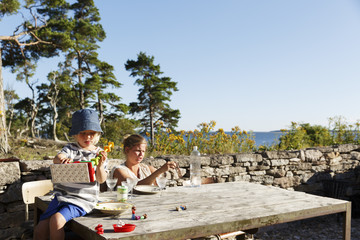 Sweden, Gotland, Bungenas, Mother and daughter (2-3) sitting at table outdoors