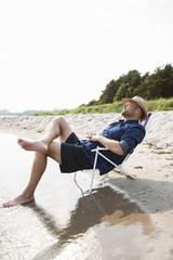 Sweden, Gotland, Mature man sitting on deckchair at seashore