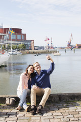 Sweden, Vastergotland, Gothenburg, Young couple sitting on promenade and taking selfie with smart phone