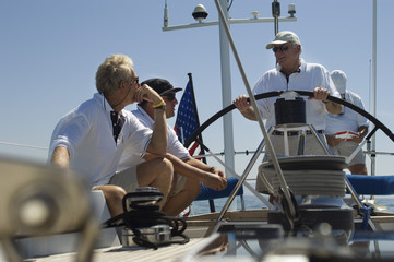 Sailors talking at the helm on a yacht against clear blue sky