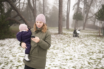 Sweden, Skane, Malmo, Young woman holding daughter (12-17 months) and using phone