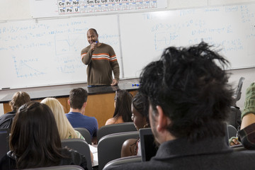 An African American male professor teaching students in the classroom