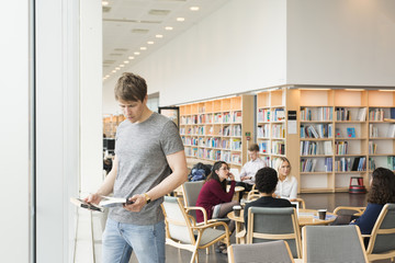 Sweden, Man standing and holding books in library