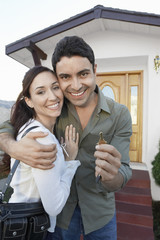 Portrait of a happy loving couple with key in front of new house