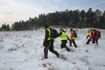 Sweden, Uppland, Upplands Vasby, Volunteers of Missing people organization walking on field covered with snow