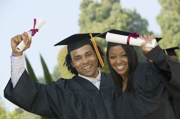 Portrait of happy students holding diplomas on graduation day