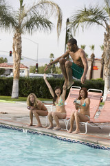Young man jumping in the pool with female friends sitting on deck chair at pool side