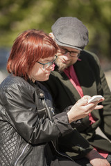 Sweden, Sodermanland, Woman with down syndrome sitting and checking smart phone together with boyfriend