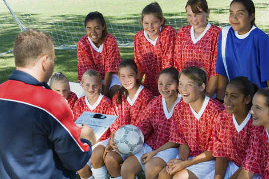 Mature male soccer coach explaining strategy to team during time out