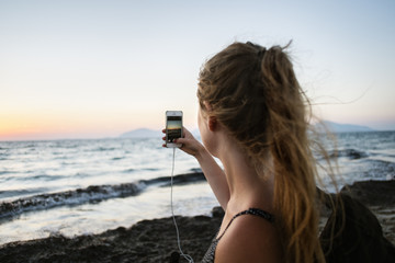 Greece, Kalymnos, Young woman photographing sunset sky with smart phone