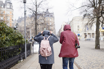 Sweden, Stockholm, Young couple walking through city in falling snow