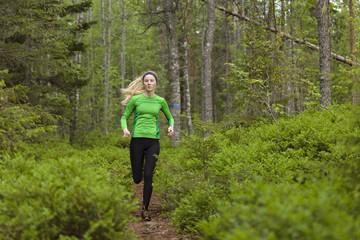 Sweden, Vasterbotten, Grossjons Nature Reserve, Woman running in forest