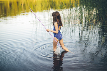 Girl holding fishing net and walking in lake