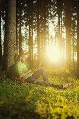 Man using laptop in the forest