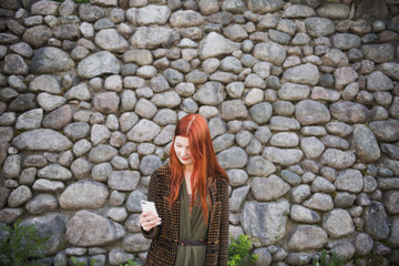 Finland, Redhaired woman standing against stone wall and using phone
