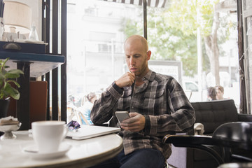 Israel, Tel Aviv, Man sitting in cafe and using phone