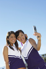 Happy Asian cheerleader with teammate taking picture through cell phone