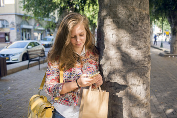 Israel, Tel Aviv, Young woman using smart phone and leaning against tree