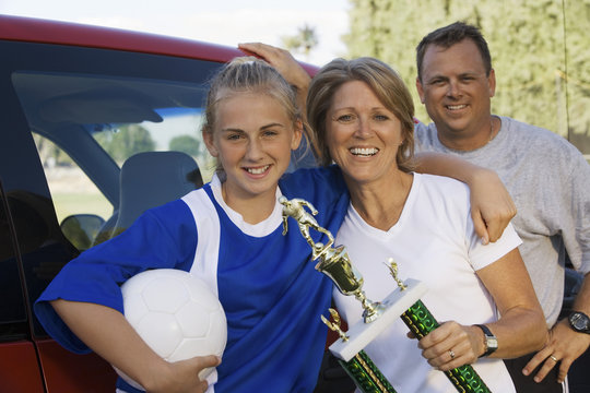 Portrait of happy parents with daughter holding soccer trophy