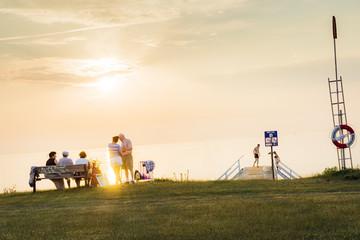 Sweden, Skane, Malmo, Sibbarp, People on grassy coastline at sunset