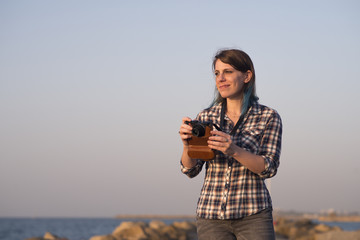 Woman holding analog camera while standing outdoors