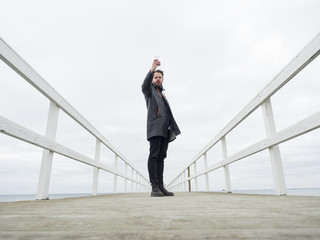 Sweden, Skane, Malmo, Man standing on pier and taking picture