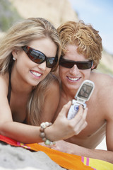 Happy young couple in sunglasses taking self-portrait through cell phone on beach