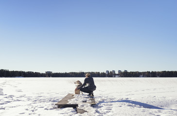 Sweden, Vasterbotten, Umea, Man with dog looking at winter landscape