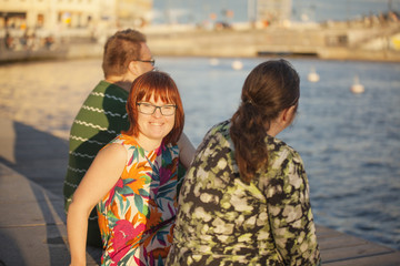 Sweden, Stockholm, Old Town, Woman with down syndrome sitting on promenade with friends