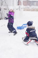 Sweden, Vastmanland, Girl (10-11) pulling brother (2-3) on sled
