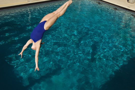 Young active female swimmer diving into the pool