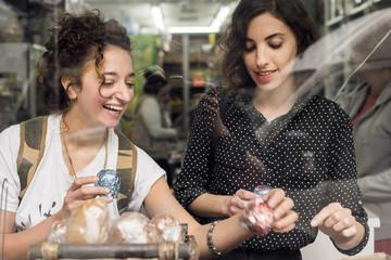 Israel, Tel Aviv, Two women choosing food