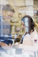 Sweden, Young couple choosing porcelain bowls in shop