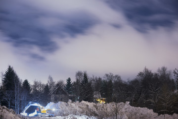 Finland, Pirkanmaa, Tampere, Excavator removing snow next to houses in forest