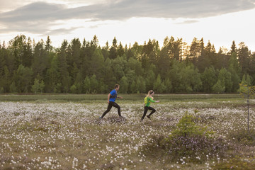 Sweden, Vasterbotten, Grossjons Nature Reserve, Man and woman running in meadow