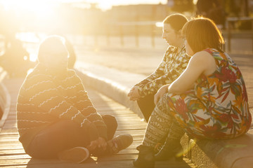 Sweden, Sodermanland, Stockholm, Sodermalm, Slussen, Woman with down syndrome sitting on promenade with friends at sunset