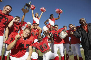 Portrait of happy football team with cheerleaders and coach celebrating success on field