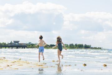 Sweden, Oland, Kopingsvik, Girl (10-11) and boy (8-9) running on beach