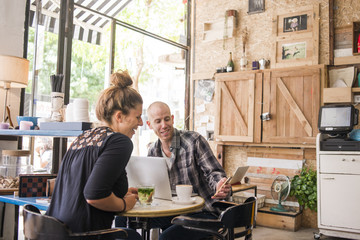 Israel, Tel Aviv, Man and woman sitting in cafe and looking at phone