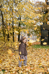Sweden, Vastergotland, Gothenburg, Leaves falling on girl (4-5) in park