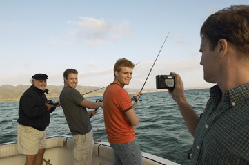 Man taking snapshot of friends fishing on yacht