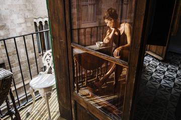 Spain, Mallorca, Las Palmas, Reflection of woman sitting on balcony