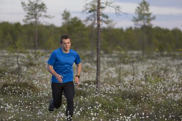 Sweden, Vasterbotten, Grossjons Nature Reserve, Man running in meadow