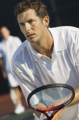 Close-up of mid adult man holding racket with partner in the background