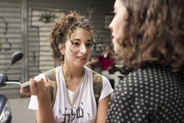 Israel, Tel Aviv, Two women talking outdoors