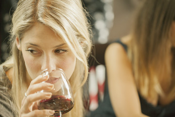 Sweden, Blonde woman drinking red wine with friend