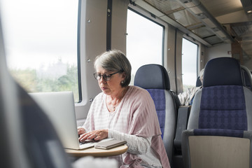 Sweden, Senior woman sitting on train and using laptop