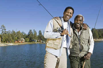 Portrait of happy senior man and adult son holding fishing rods by lake