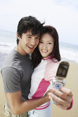 Loving middle aged couple taking self-portrait through cell phone on beach