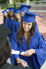 Group of female graduates collecting certificate from female dean